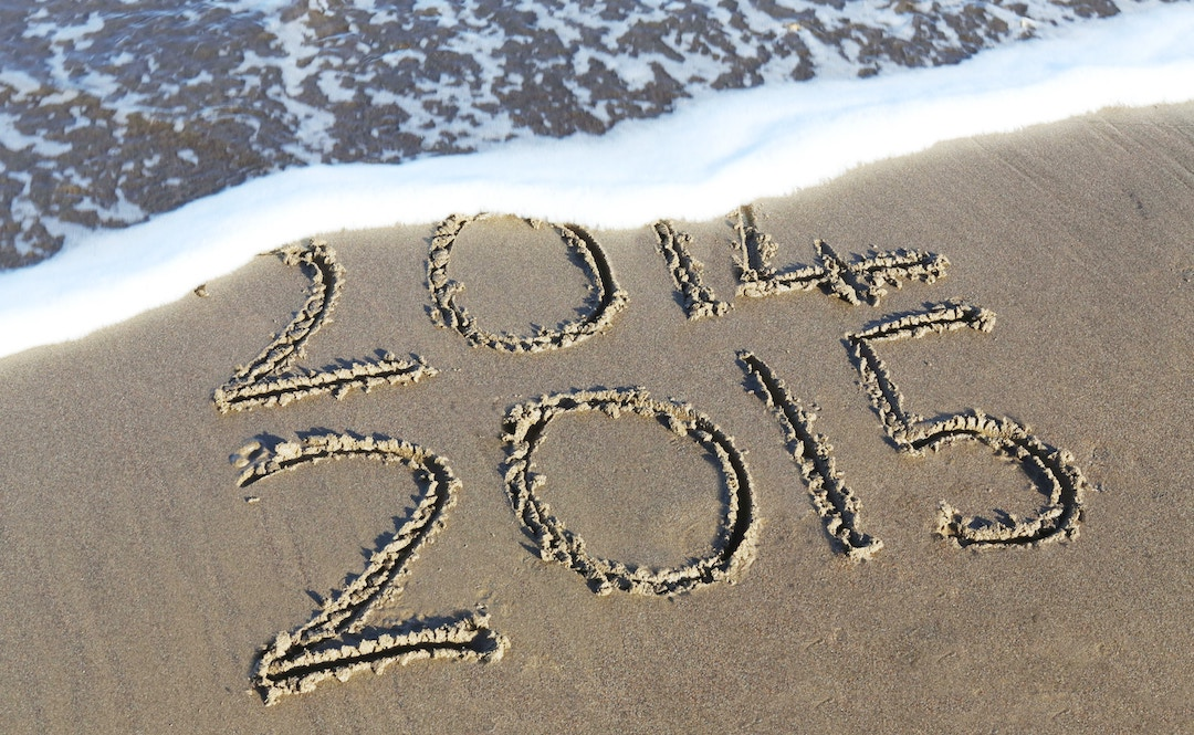 """Image of the numbers """"2014"""" and """"2015"""" written in the sand"""