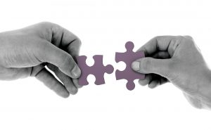 Image of hands holding two puzzle pieces