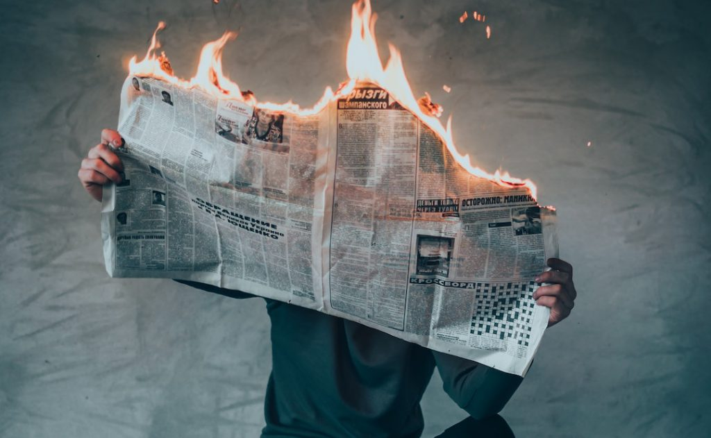 Image of man holding burning newspaper