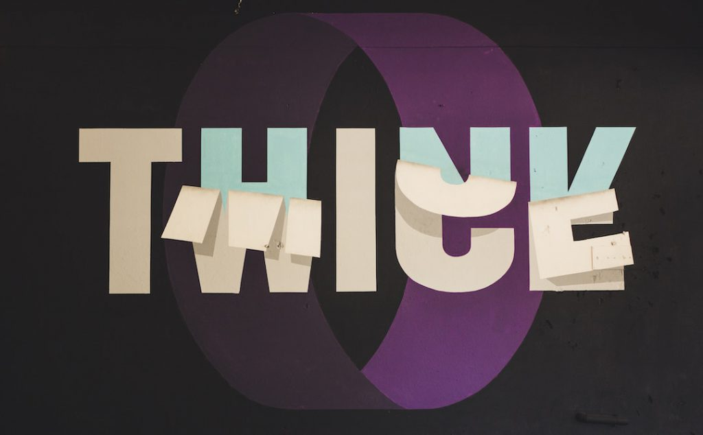 "Image of the word ""think"" with the word ""twice"" peeling away"