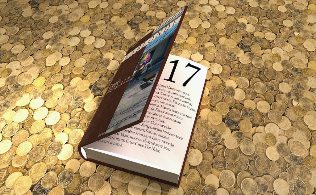 Image of the number 17 on page in a book. Book resting on gold coins.