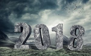 "Image of ""2018"" in stone against a mountain scene"