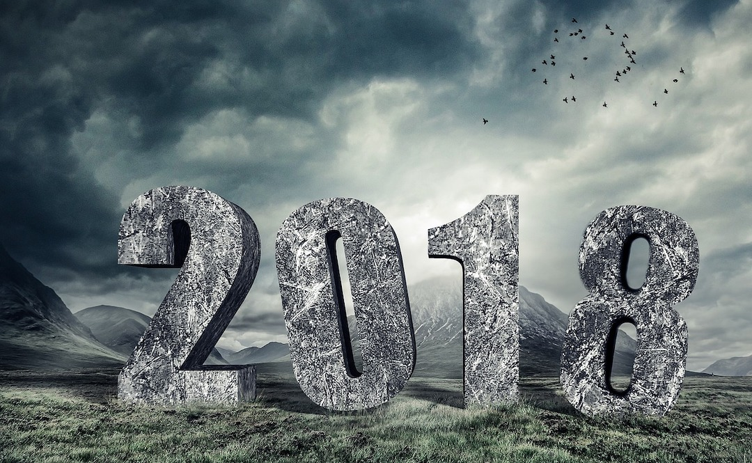 """Image of """"2018"""" in stone against a mountain scene"""