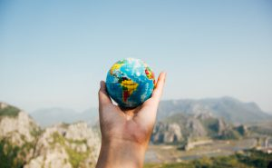 Image of hand holding a globs of the world